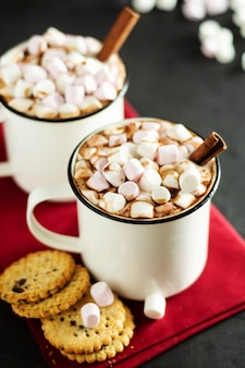 Two cups of hot chocolate, cocoa or warm drink with marshmallows and sweet cookies on dark