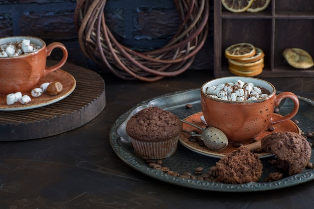 Two cups of hot chocolate with marshmallows and muffins close up