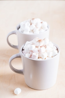 Two cups of hot cocoa with marshmallows on wood table
