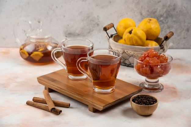 Due tazze di tè caldo e bastoncini di cannella su tavola di legno.
