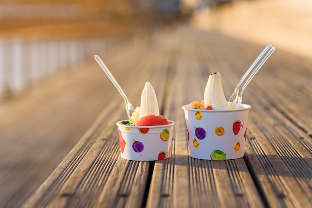 Two cups of ice cream with candies on sunset.
