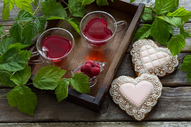 ラズベリードリンクとハートの形をした2つのクッキーとハートの形の2つのカップ