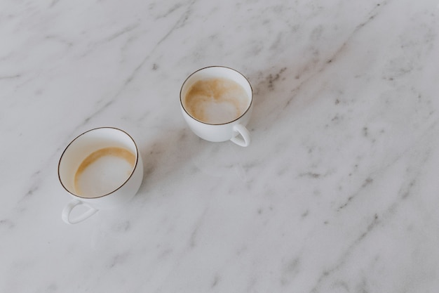 Two cups of latte on a marble table