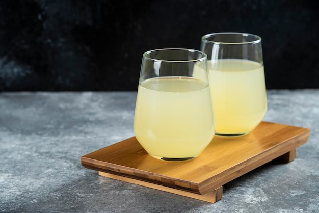 Two cups of lemonade on wooden table.