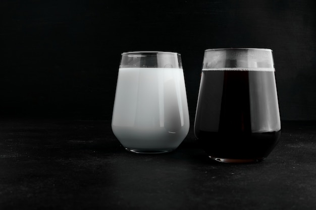 Two cups of milk and dark espresso on black background.