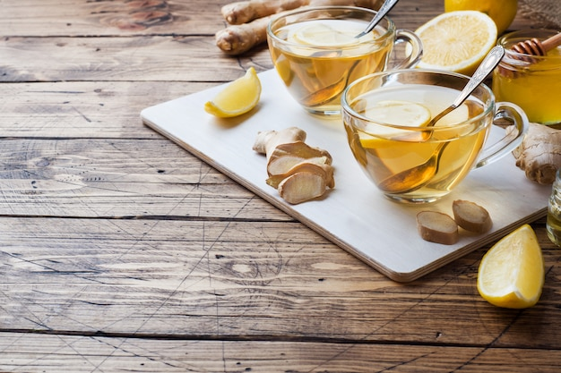 Two cups of natural herbal tea ginger lemon and honey copy space