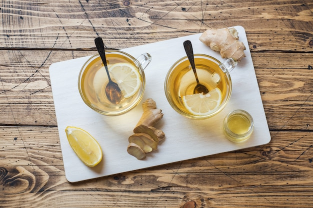 Two cups of natural herbal tea ginger lemon and honey on a wooden surface.