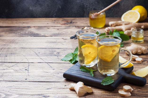 Two cups of natural herbal tea ginger lemon mint and honey on a wooden surface.