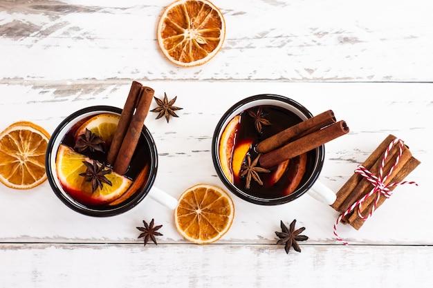 Две чашки осеннего глинтвейна или глинтвейна со специями и дольками апельсина на деревенском взгляде на столешницу. традиционный напиток на осенне-зимний праздник.