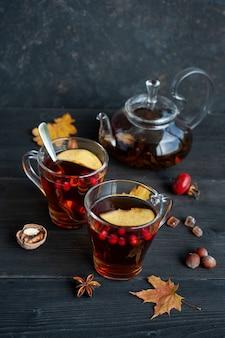 黒い木製にベリーとリンゴのかけらが入った秋の温かいお茶2杯