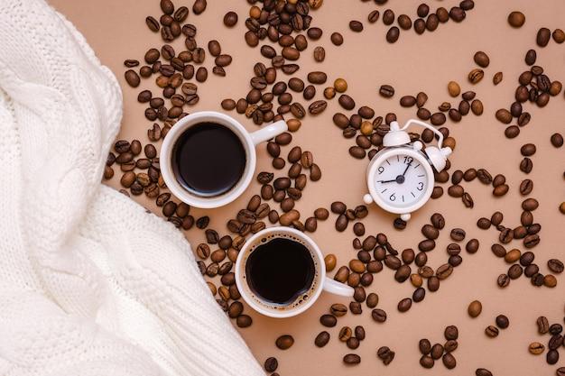 ベージュの背景にブラックコーヒー、目覚まし時計、白いセーター、コーヒー豆の2つのカップ。居心地の良いデートとウェルネス。上面図