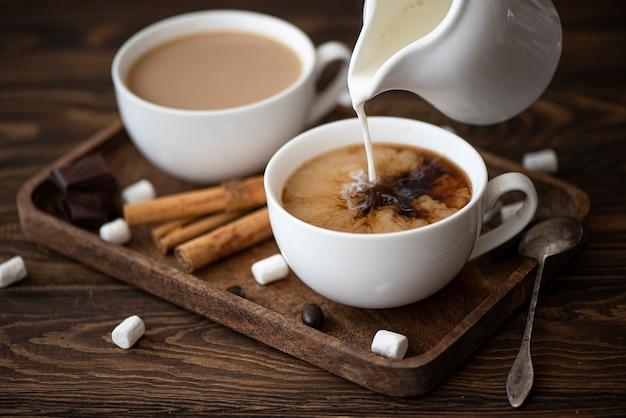 Две чашки черного кофе с молоком на подносе