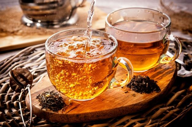 Две чашки черного чая на плетеном столе рано утром. чайное утро на рассвете. процесс розлива чая.