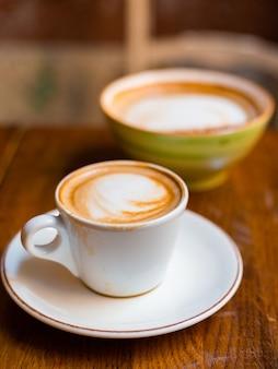 木製の背景にラテアートとカプチーノの2つのカップ。簡単な朝食のコンセプト。大小のセラミックカップ