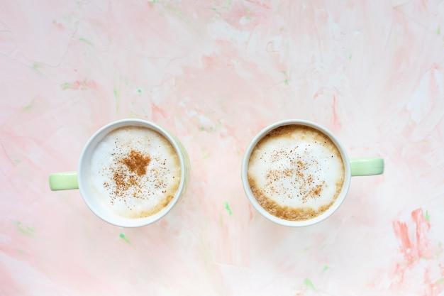 밝은 분홍색 소박한 벽에 계 피 매운 된 라 떼 커피 두 잔. 평평하다, 평면도, 복사 공간, 소셜 미디어 영웅 헤더 템플릿.
