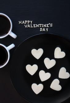 Две чашки кофе и шоколадные конфеты с белым в форме сердца - надпись happy valentine