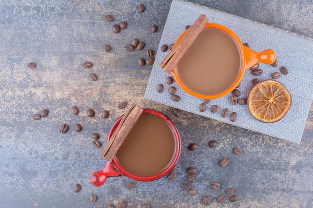 돌 테이블에 커피, 책, 커피 콩 두 잔. 고품질 사진