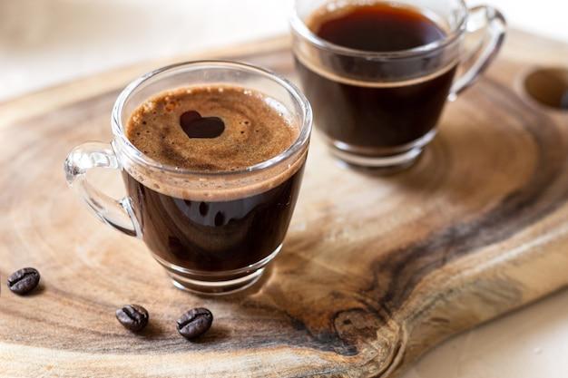 ハート型のコーヒーエスプレッソ2杯と木製の背景にコーヒー豆クローズアップ