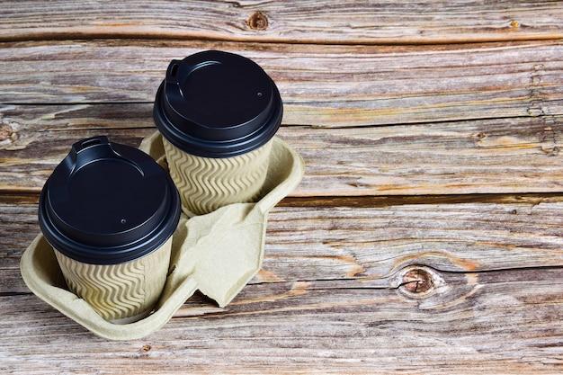 Две чашки кофе из одноразовых стаканов на декоративной подставке