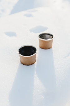 Две чашки кофе на снегу в лесу.
