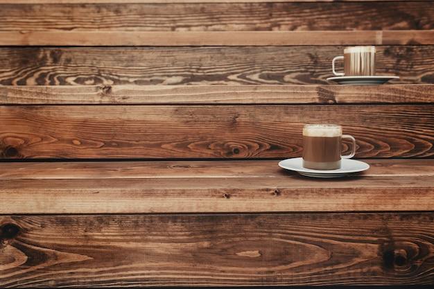 Две чашки кофе на фоне деревянной коричневой террасы. фото высокого качества