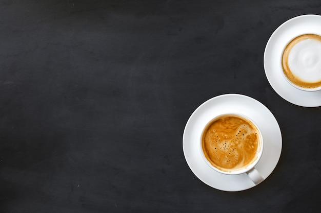 Две чашки кофе в белых чашках на черной поверхности