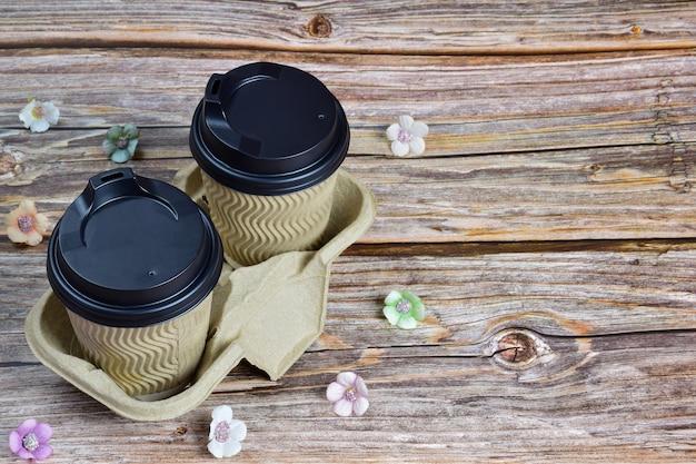 나무 배경의 프레임 왼쪽에 있는 장식용 스탠드에 커피 두 잔