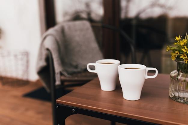 Две чашки кофе на столе на деревянной коричневой террасе во время вечернего заката. расслабление, концепция жизни тихой сельской местности. прекрасная пара вечеров