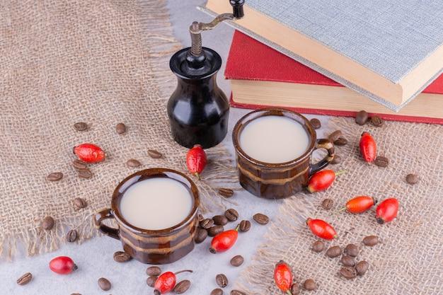 Две чашки кофе с зернами и плодами шиповника на мешковине. фото высокого качества