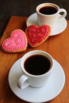 木製のテーブルにハート型のロイヤルアイシングクッキーとコーヒー2杯
