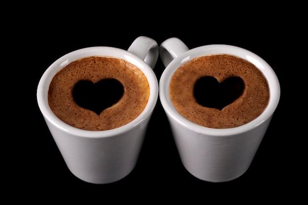 Две чашки кофе с сердечками в сливках