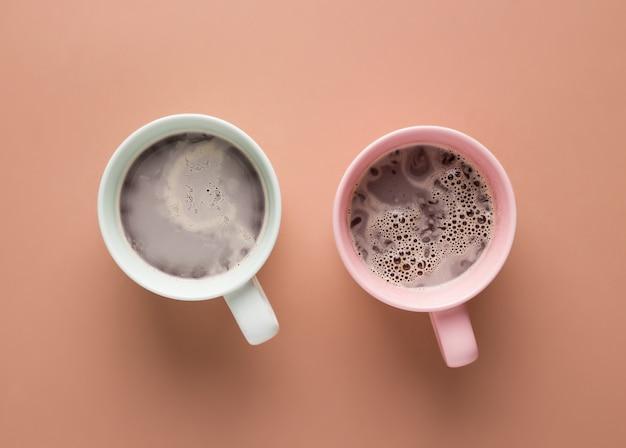 茶色の背景にピンクとミント色のミルクとコーヒーを2杯