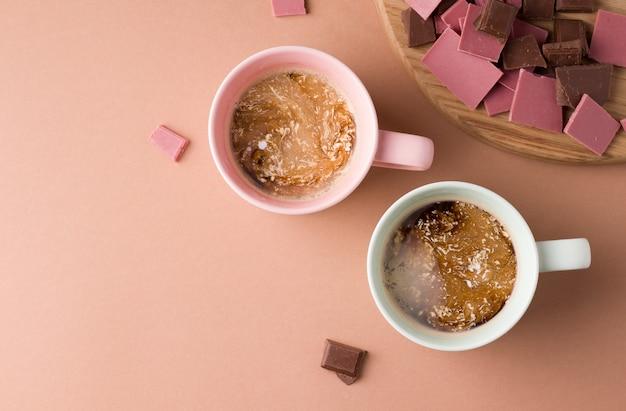 チョコレートの横にある茶色の背景に牛乳とコーヒーを2杯