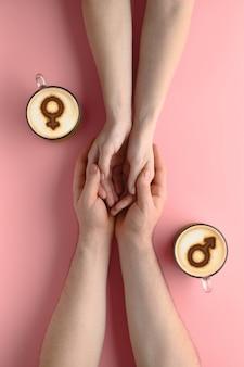 우유 거품에 금성과 화성의 상징과 파스텔 핑크 배경에 사랑에 한 쌍의 손을 잡고 커피 두 잔. 발렌타인 데이에 개념 낭만적 인 날짜입니다. 평면도, 크리에이티브 플랫 레이