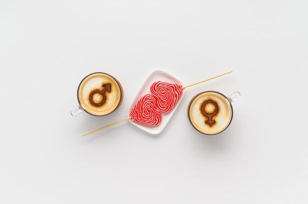 Две чашки кофе с символами венеры и марса на взбитой молочной пене и пара леденцов на палочке в форме сердца