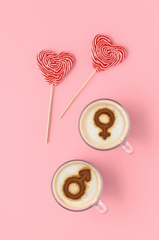 Две чашки кофе с символами венеры и марса на взбитой молочной пене и пара леденцов