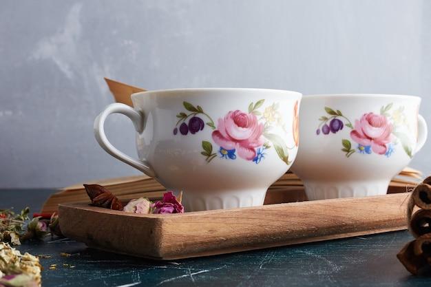Две чашки напитка на деревянной тарелке.