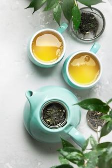 灰色のコンクリートテーブルの上のティーポットと緑茶2杯