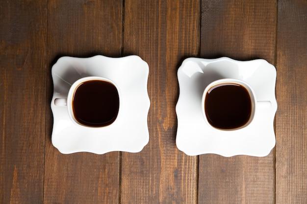 접시에 뜨거운 블랙 커피 두 잔. 나무 배경. 위에서