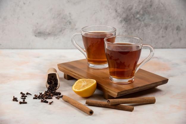 Две чашки горячего чая на деревянной доске с палочками корицы.