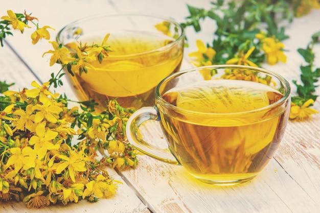 木製のグランジテーブルにオトギリソウ(ツッサン)茶2杯