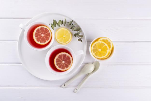 赤いフルーツとレモンスライス、上面とハーブティーの2つのカップ