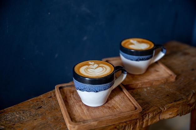木製のテーブルの背景にラテアートとおいしいカプチーノの2カップ