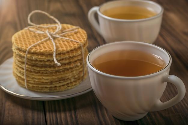 나무 테이블에 차 두 잔과 홈메이드 와플. 차와 함께 만든 수제 케이크.