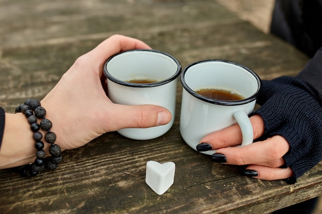 Две чашки чая на природе в руках пары в черных перчатках на деревянной поверхности