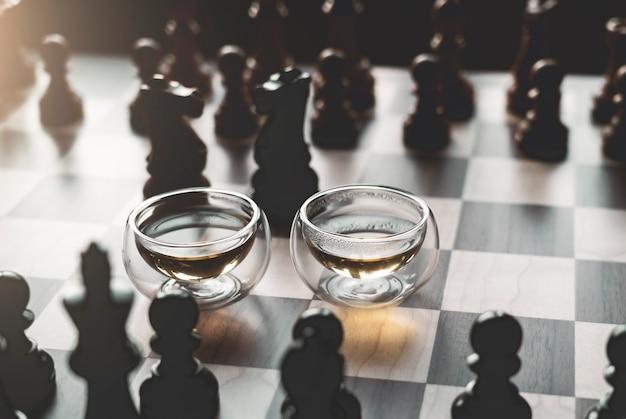温かみのある色調、家庭的で居心地の良いシーンの背景を持つチェス盤にお茶を2杯