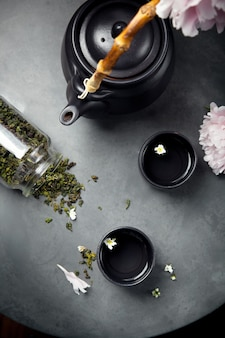 Two cups of oolong green tea with teapot, set with peionies, overview, selective focus. dark style photo.