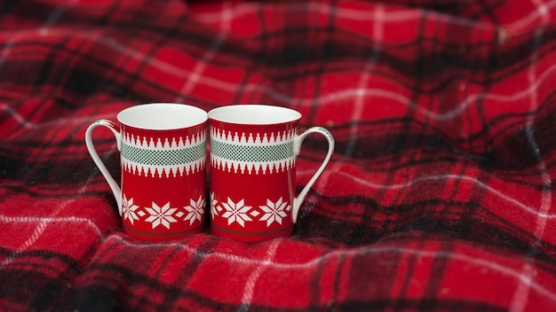 Two cups patterned stand on blankets