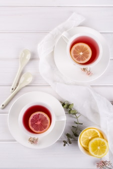 Two cups of red fruit and herbal tea with lemon slice, top view