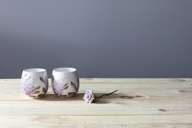 Two cups and rose on wooden table